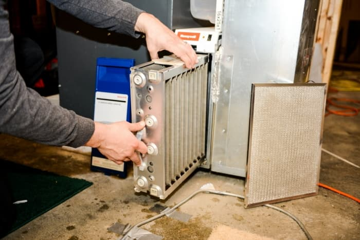 man removes a electronic air cleaner from furnace.
