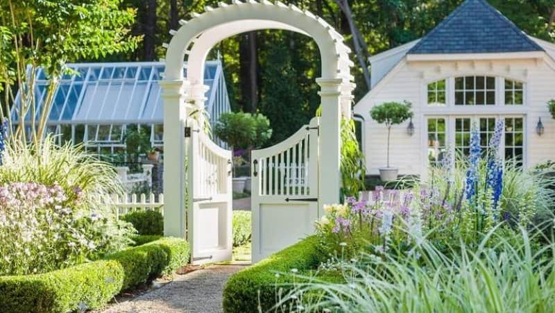Sidewalk walkway with arch leading to front of home