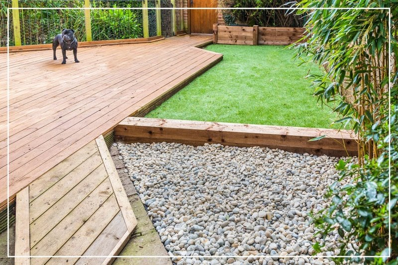 turf backyard with wood and rock accents (Photo by Christine Bird / Shutterstock.com)