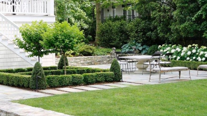 Backyard landscaping with patio table and chairs next to grass