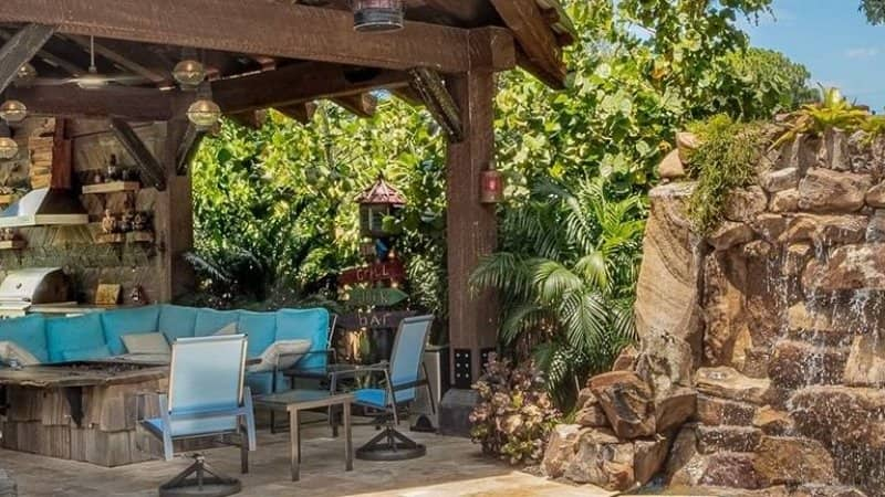 Outdoor area with grill and furniture around fire pit and rocky waterfall