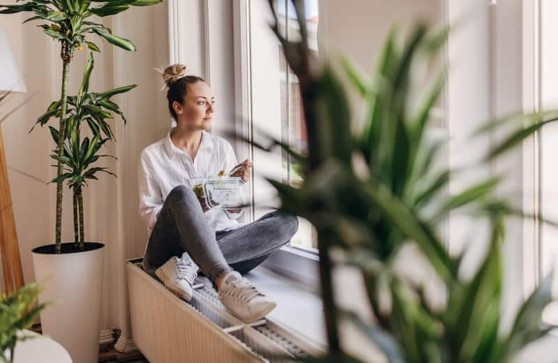 woman sitting by window and eating  (Photo by South_agency/iStock/Getty Images Plus via Getty Images)