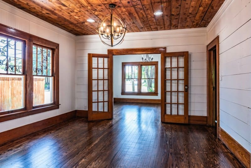 Craftsman-style living room with shiplap walls, original shiplap ceiling, and hardwood floors (Photo by AdrieDee - stock.adobe.com)
