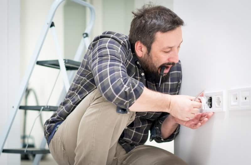 Man fixing electrical outlet (Photo by Jasmin Merdan / Moment via Getty Images)