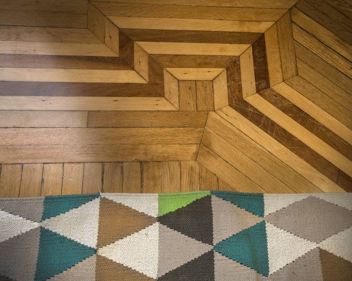 A bold geometric rug pattern and unique flooring adds visual interest. (Photo by Frank Espich)