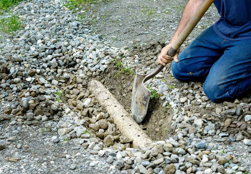 Person installing a French drain (Photo by KQ Ferris - stock.adobe.com)