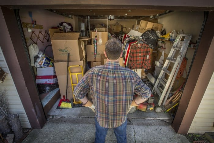 Guy staring into garage packed with boxes and other items.