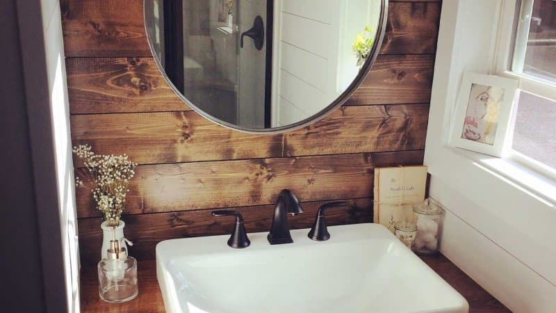 Small bathroom sink, wood shiplap accent wall, and circle mirror (Photo by Michael - stock.adobe.com)