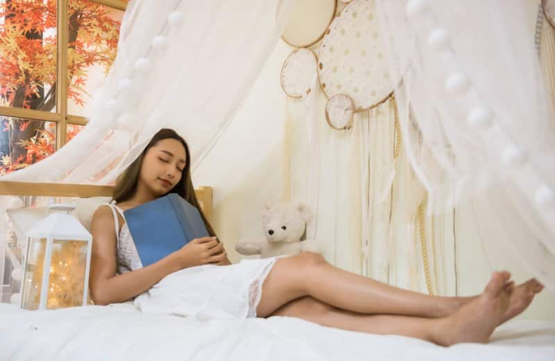 girl taking a nap in bedroom with book on lap (Photo by blanscape/iStock/Getty Images Plus via Getty Images)