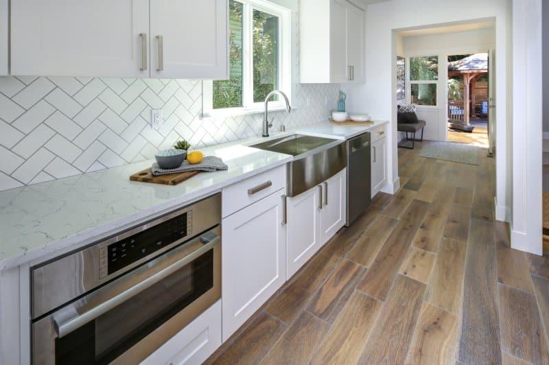 Kitchen with white herringbone backsplash and white cabinets (Photo by Javani LLC - stock.adobe.com)