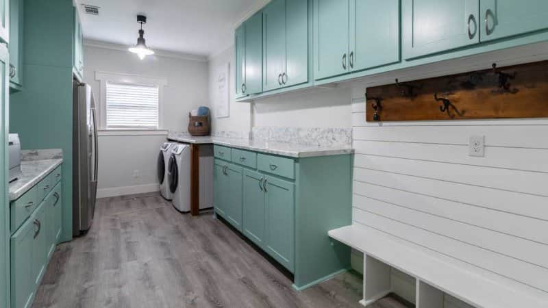 Mint green and white laundry room with a white shiplap bench (Photo by AdrieDee - stock.adobe.com)
