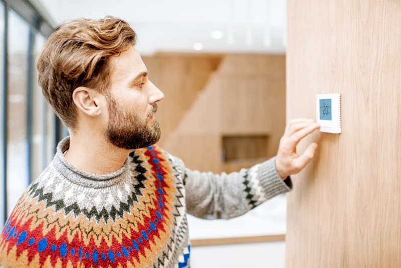 Man adjusting the temperature on the thermostat (Photo by Rh2010 - stock.adobe.com)