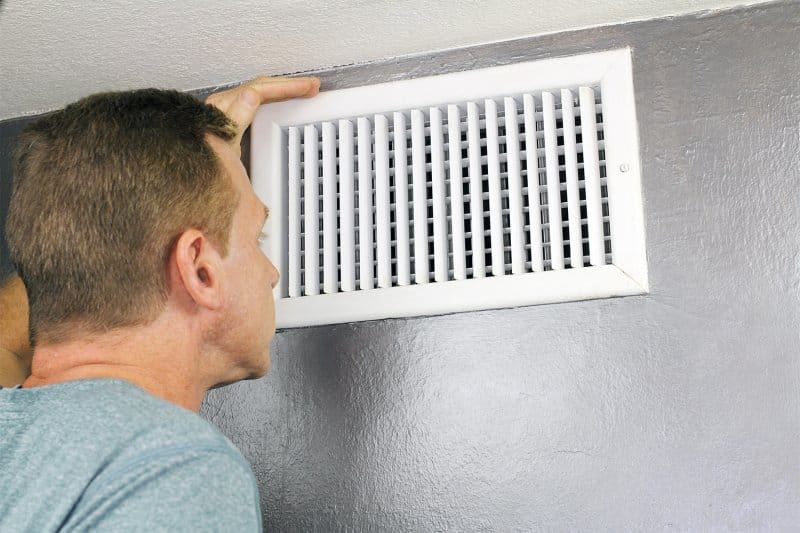 Man inspecting air vent in home (Photo by  Serenethos via Getty Images)