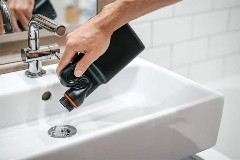 Plumber using chemicals to clean sink drain (Photo by Galaganov - stock.adobe.com )