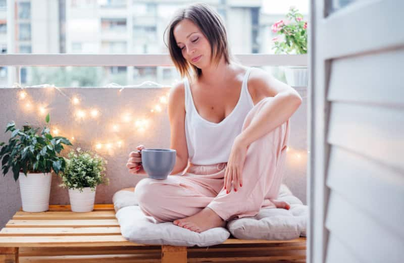 woman drinking coffee on outdoor patio (Photo by petrunjela/iStock/Getty Images Plus via Getty Images)