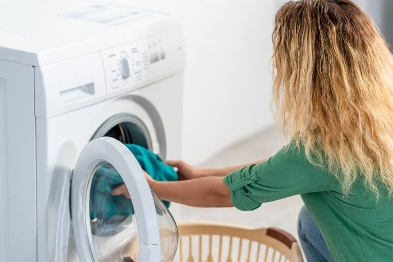 Woman putting laundry in the washing machine (Photo by Sondem - stock.adobe.com)