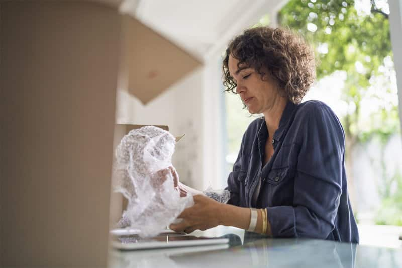 Woman wrapping belongings in bubble wrap for moving (Photo by Portra/Digital Vision via Getty Images)