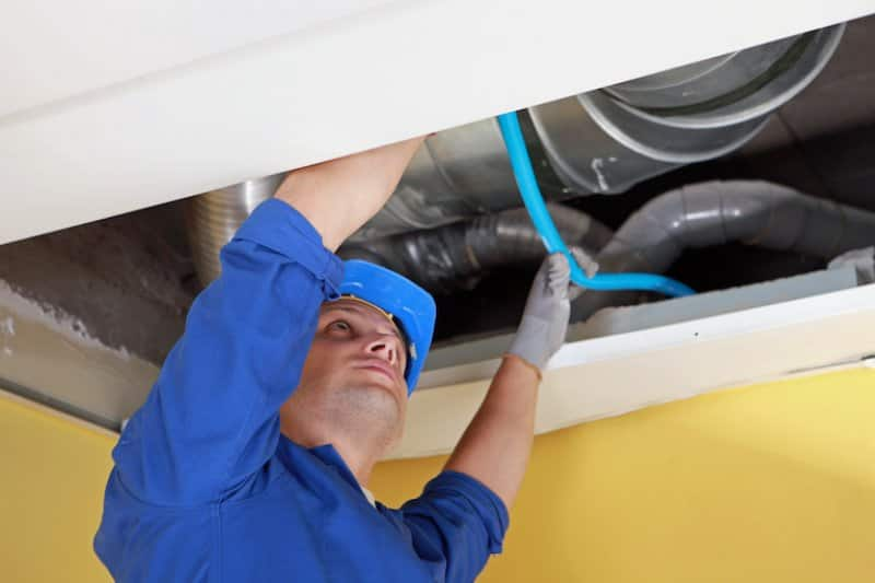 man reaches into ceiling air duct for replacements (Photo by © auremar - stock.adobe.com)