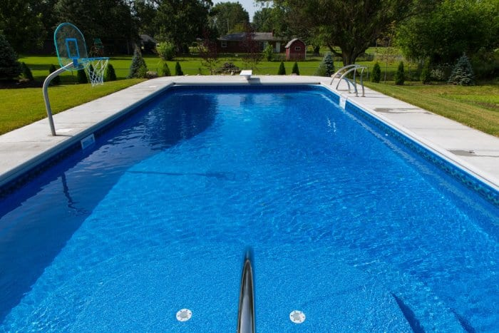 Rectangle in-ground pool with diving board and basketball goal