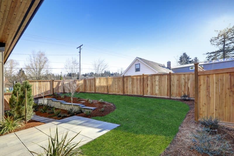 back yard with wood privacy fence, green grass, landscaping with mulch and concrete (Photo by Iriana Shiyan - stock.adobe.com)