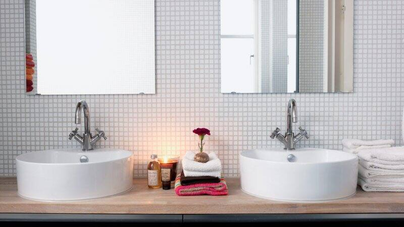 A bright bathroom with double sinks and white tiles (Photo by  Carlsson, Peter via Getty Images)
