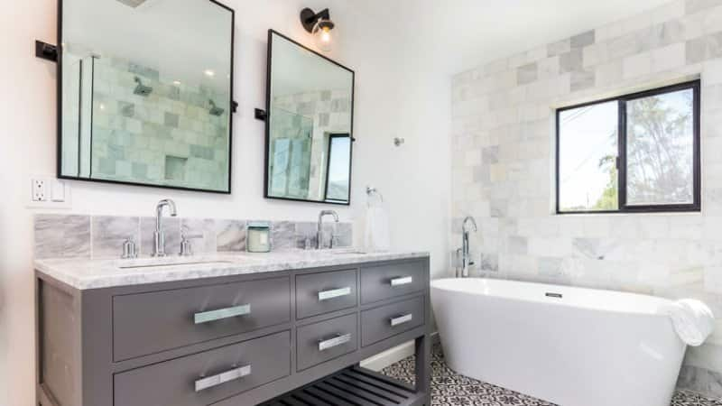 Twin sinks and mirrors in bathroom with white bathtub