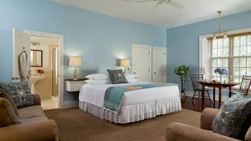 A bedroom with blue walls (Photo by Jon Lovette/DigitalVision via Getty Images)