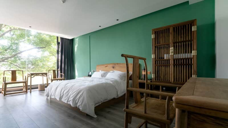 Wooden furniture in a green painted bedroom (Photo by zhihao/Moment via Getty Images)