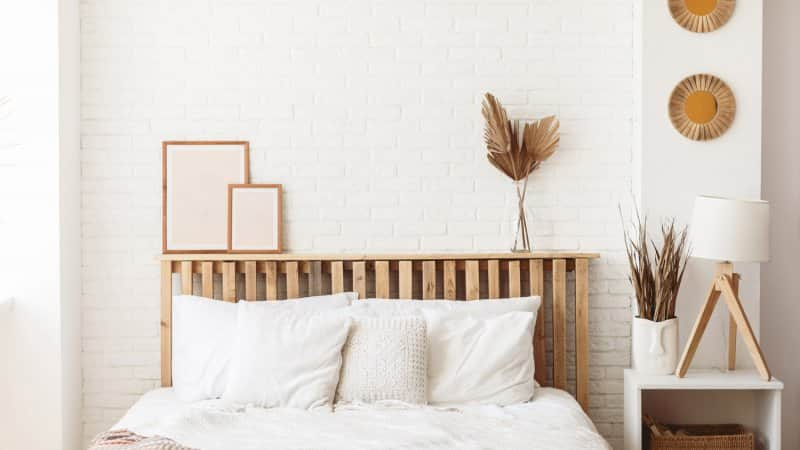 A bed with wooden headboard in an off-white painted bedroom (Photo by Anastasiia Krivenok/Moment via Getty Images)