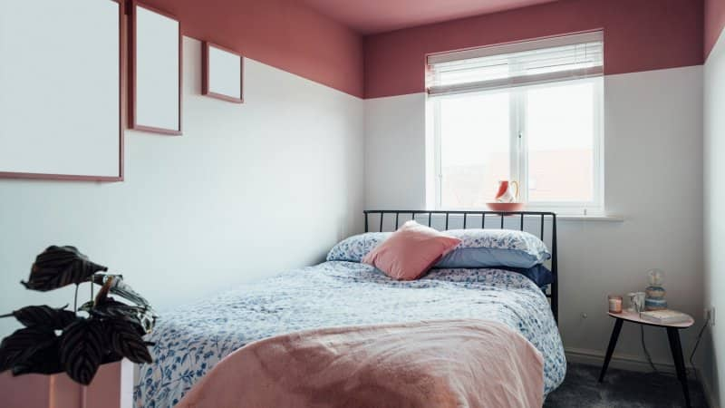A bedroom with white walls and pink ceiling (Photo by SolStock/E+ via Getty Images)