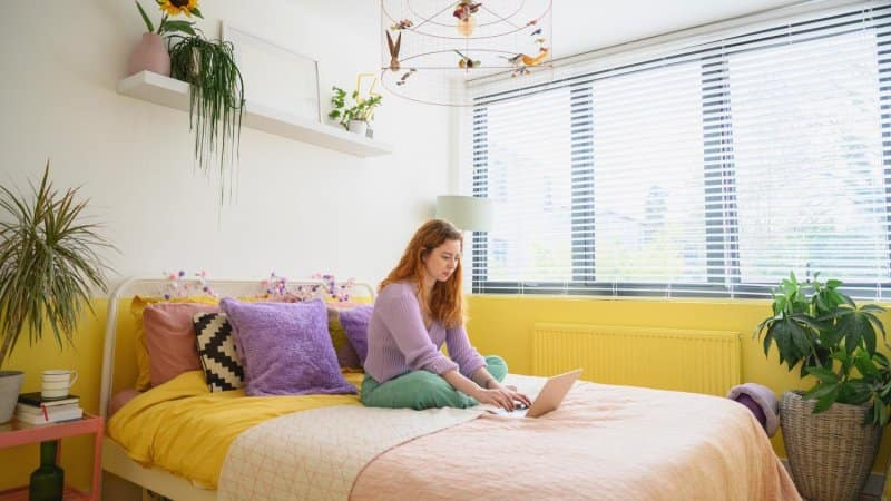 Woman relaxing in her yellow painted bedroom with her laptop (Photo by JohnnyGreig/E+ via Getty Images)