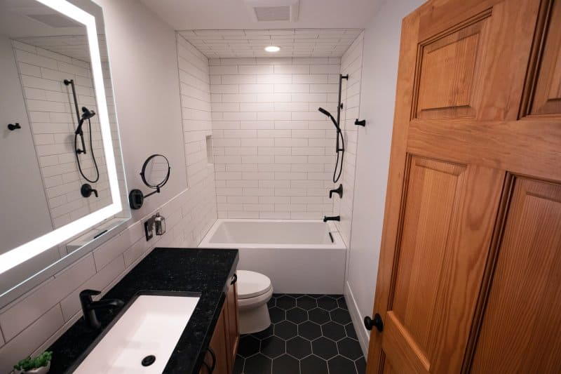 Bathroom with black honeycomb tile floor, black vanity, matte black fixtures, subway tile shower wall, and lighter mirror (Photo by filo / iStock / Getty Images Plus via Getty Images)