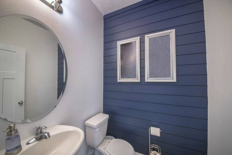 Powder room with navy blue shiplap accent wall (Photo by Jason – stock.adobe.com)
