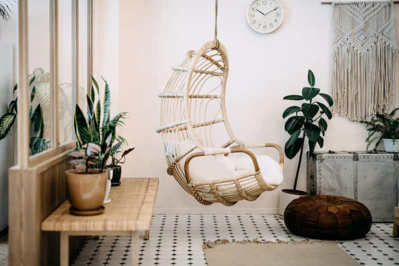 home interior with white, cream, and light wood bohemian decor with hanging chair in middle (Photo by AsiaVision/E+ via Getty Images)