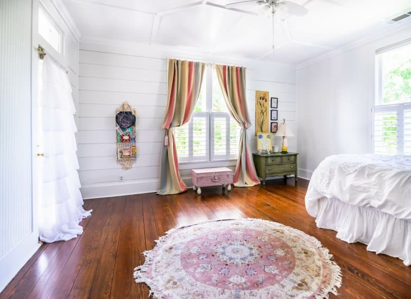 Bedroom with white shiplap walls, hardwood floors, tassel rug, and ruffled white and colorful striped curtains (Photo by AdrieDee - stock.adobe.com)