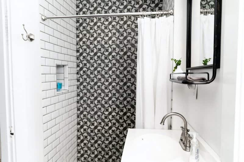 Modern shower with white subway tile wall next black-and-white tile wall (Photo by Andrea Davis on Unsplash )
