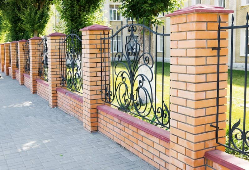 a tan brick fence with alternating metal grille design and stone sidewalk (Photo by olgavolodina - stock.adobe.com)