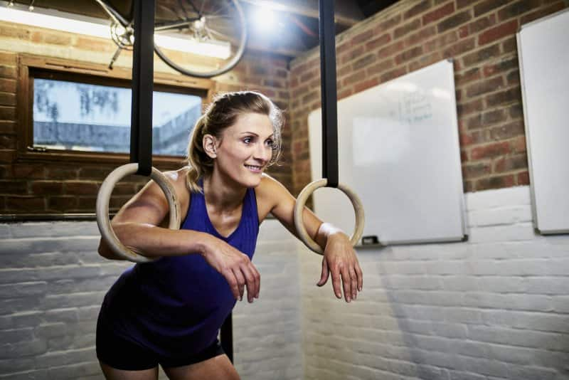 Woman in gym clothes with her arms through gymnastic rings in garage home gym and lights hanging in the background (Photo by Justin Lambert / DigitalVision via Getty Images)