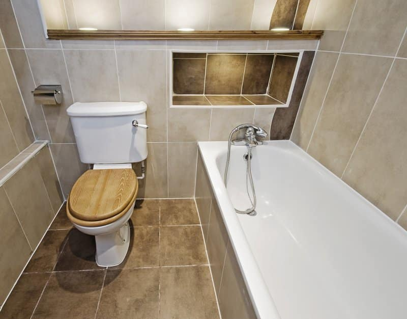 Brown tile bathroom with built-in shower shelves above tub (Photo by yampi – stock.adobe.com)