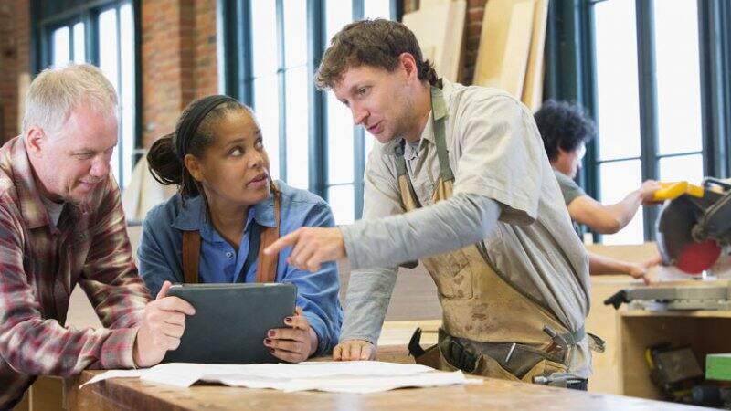 Carpenter using tablet in workshop with team members