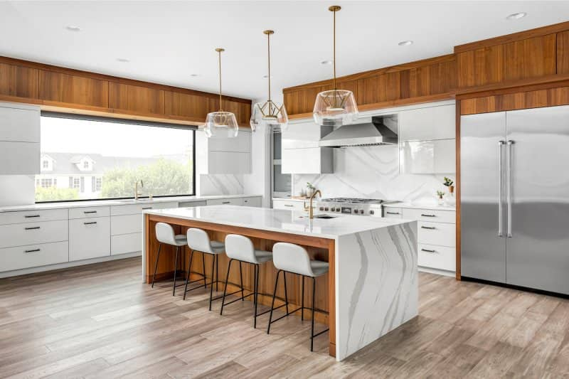 Kitchen with white marble backsplash, marble waterfall island and white cabinets (Photo by bmak - stock.adobe.com)