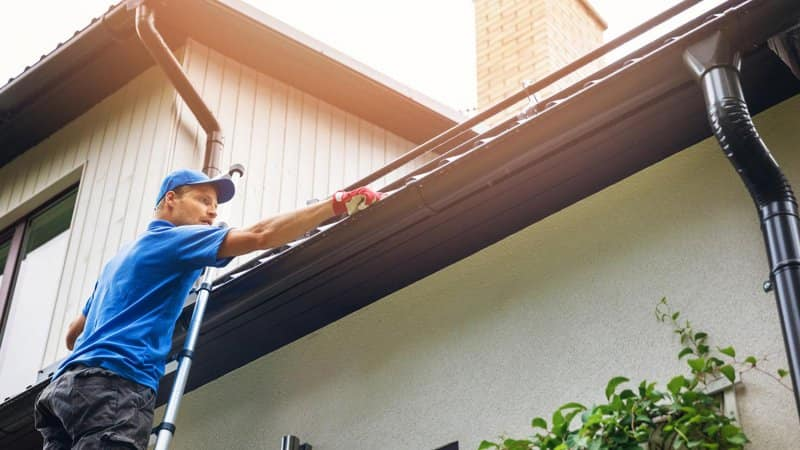 man on ladder cleaning house gutter (Photo by ronstik / iStock / Getty Images Plus via Getty Images)