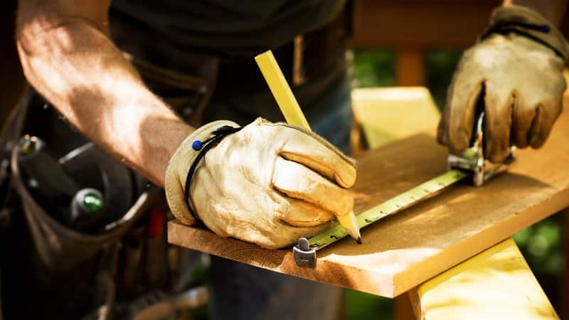 Close-up of a carpenter's hands in gloves measuring a wooden plank (Photo by stevecoleimages/E+ via Getty Images)