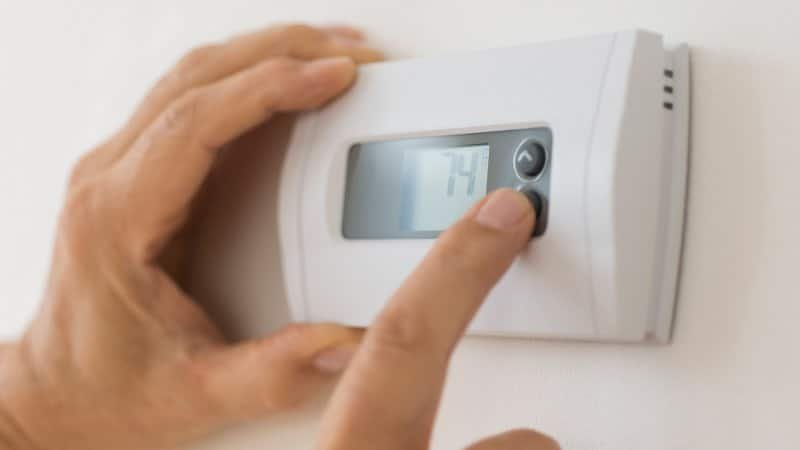 Close-up of a person's hand adjusting the temperature by using a thermostat (Photo by Tetra Images via Getty Images)