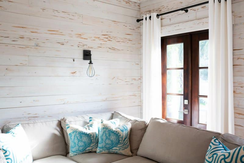 Beach-themed living room with gray couch, nautical throw pillows and white weathered shiplap walls (Photo by KCULP - stock.adobe.com)