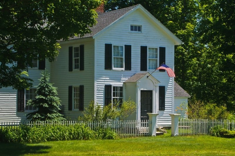 Colonial style house with flag (Photo by KenWiedemann / E+ via Getty Images)