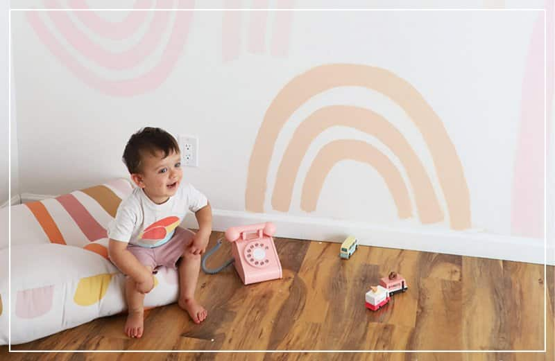 baby sitting on cushion in room with orange arches on wall  (Photo by © A Bubbly Life)