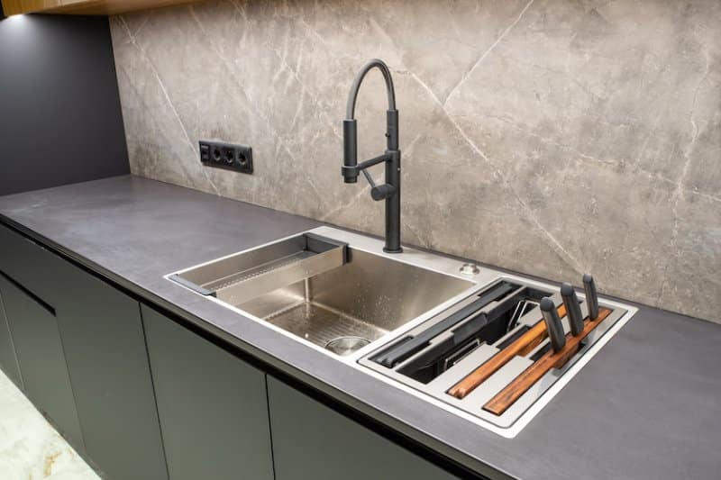 industrial style kitchen with concrete countertop, large stainless steel sink, and dark gray cabinets (Photo by  Aleksandr_Kendenko via Getty Images)