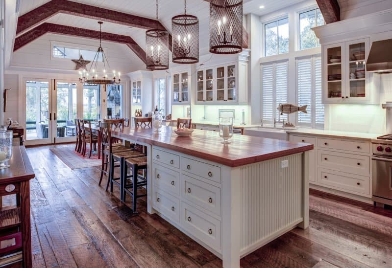 Farmhouse/craftsman kitchen and dining room with hardwood floors, exposed beams, shiplap ceiling, and big center island (Photo by Wollwerth Imagery - stock.adobe.com)