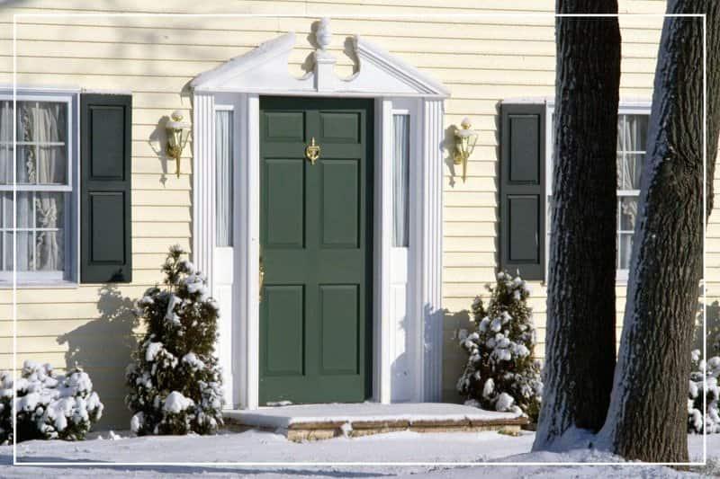 dark green front door in winter  (Photo by Jupiterimages/liquidlibrary via Getty Images)